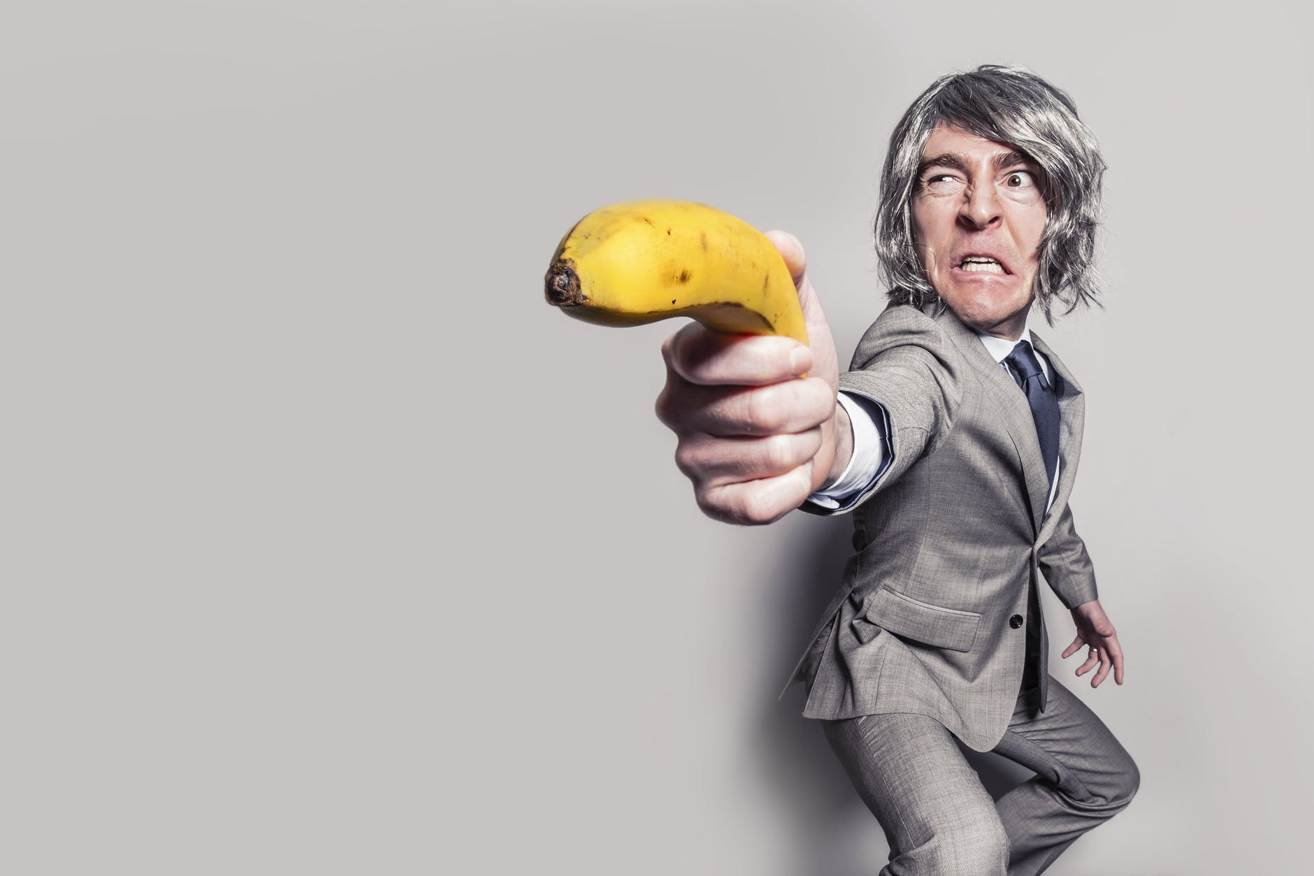 man in gray suit jacket holding yellow banana fruit while making face