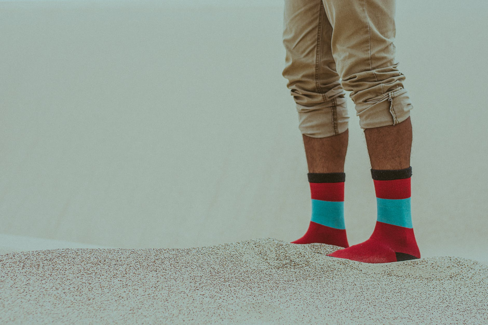 person wearing red socks walking on sand