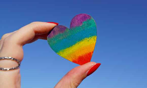 photo of person holding multicolored heart decor