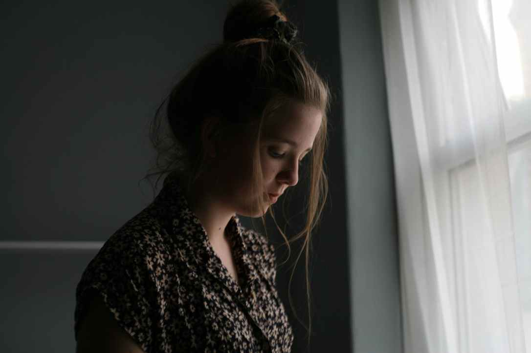 woman standing beside window curtain