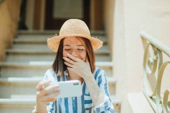 photo of woman smiling while siting on stairs and using white smartphone