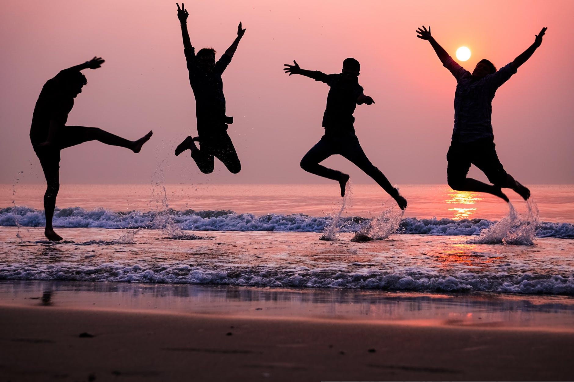 photo of people doing jump shot on beach