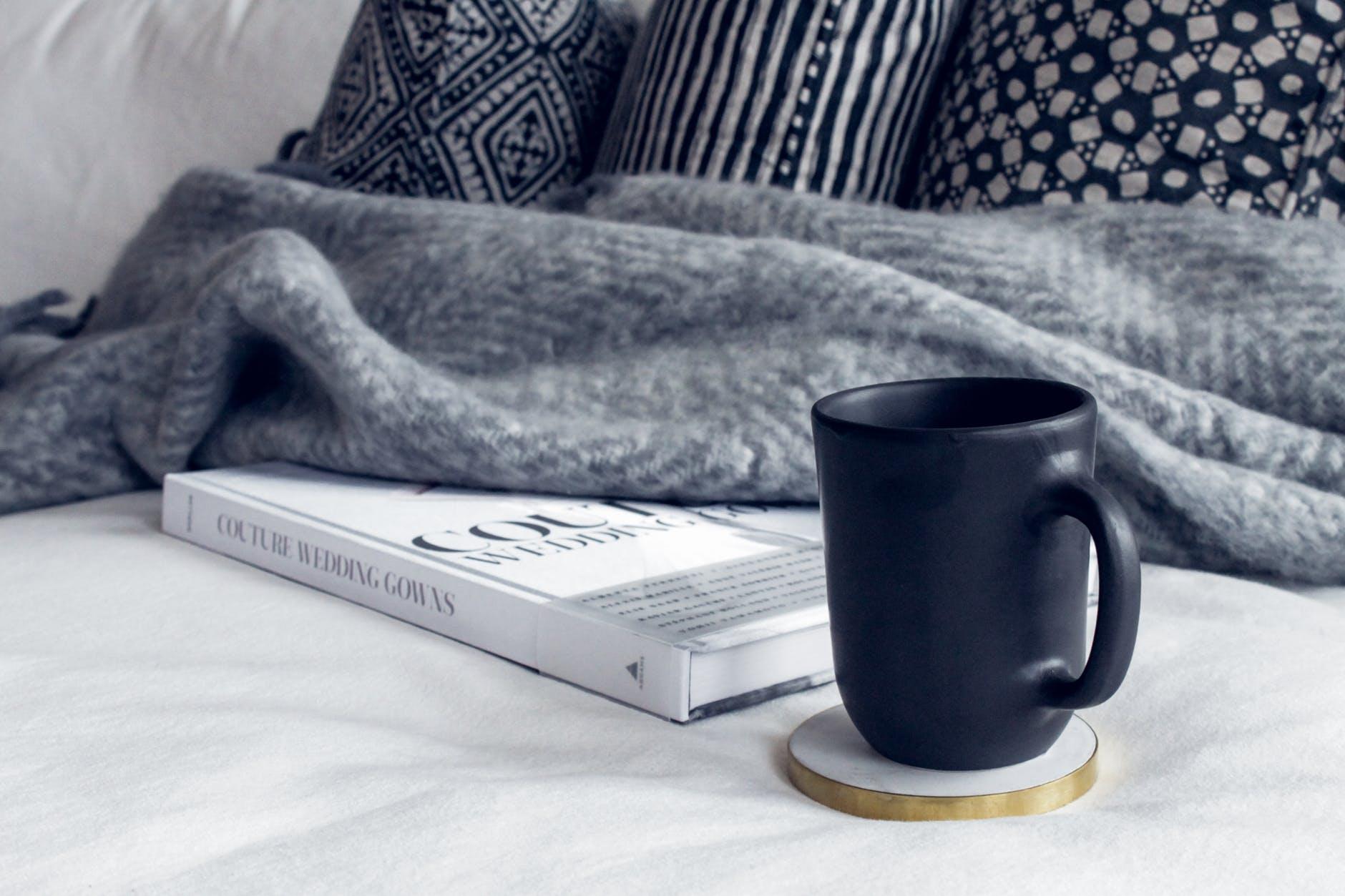 black ceramic mug on round white and beige coaster on white textile beside book