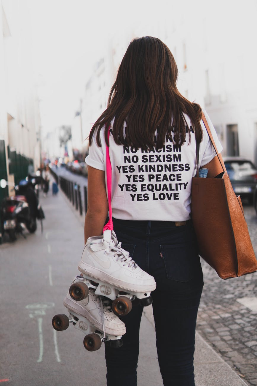 woman in white shirt and denim jeans carries skate shoes and tote bag