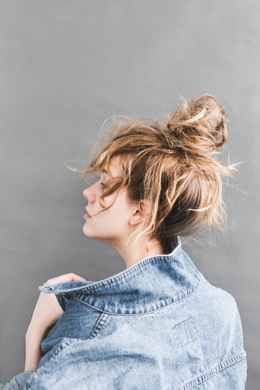 back view of woman holding her denim jacket
