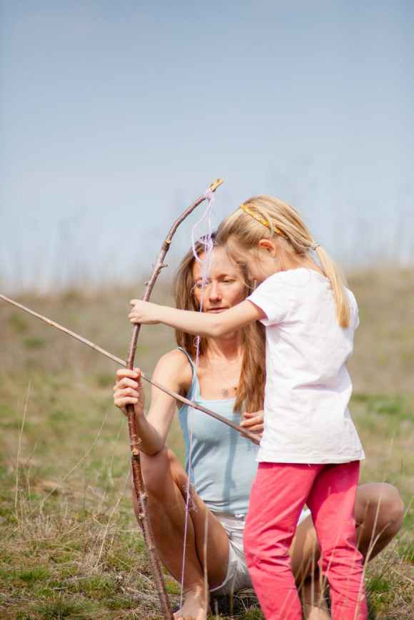 photo of woman teaching her child on how to use bow and arrow