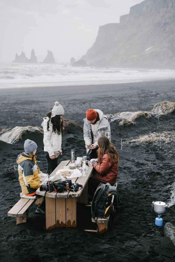 people gathering together on cold sea beach for picnic