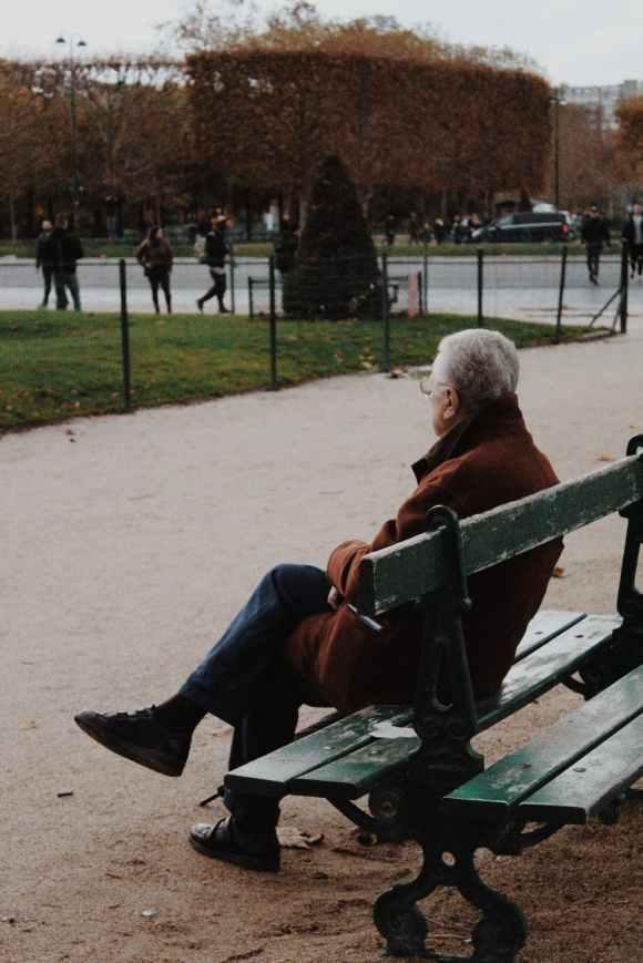 elderly man sitting on bench in park during autumn day