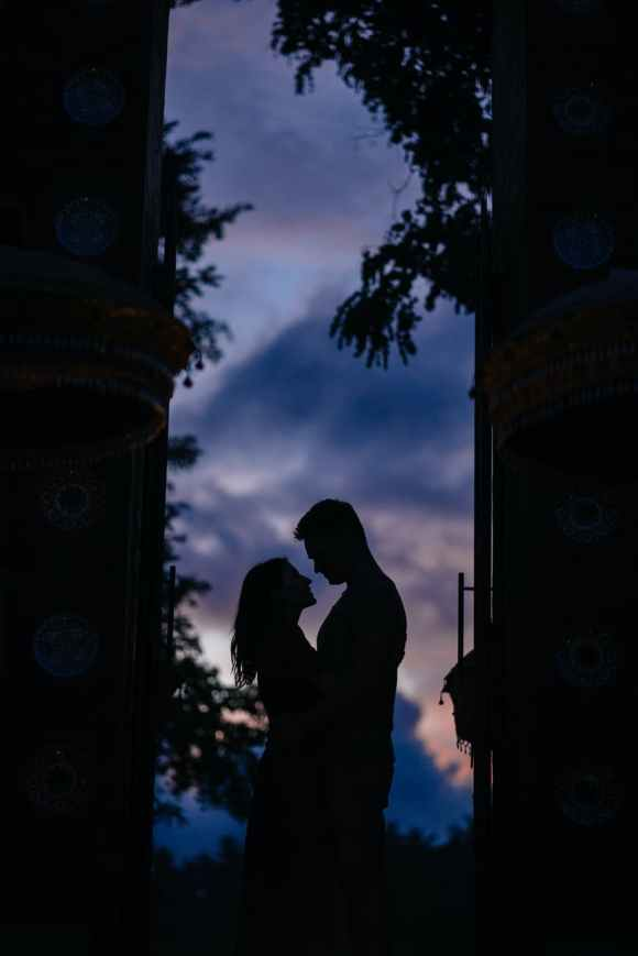 silhouettes of hugging couple standing in arch in darkness